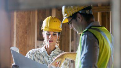 Um homem e uma mulher, em uma construção olhando para uma planta de construção
