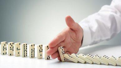 Mão humana interrompendo o fluxo de queda de uma fila de dominós