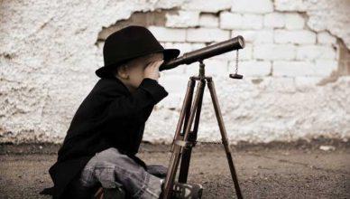Criança olhando por uma luneta